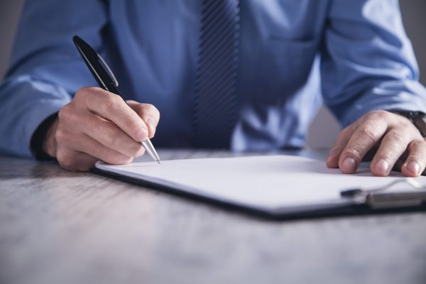 Businessman signing a document on a clip board